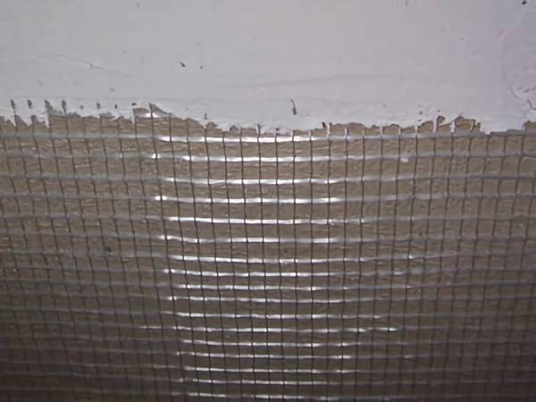 A big galvanized steel mesh panel is plastering on the wall and the cement in on the mesh.