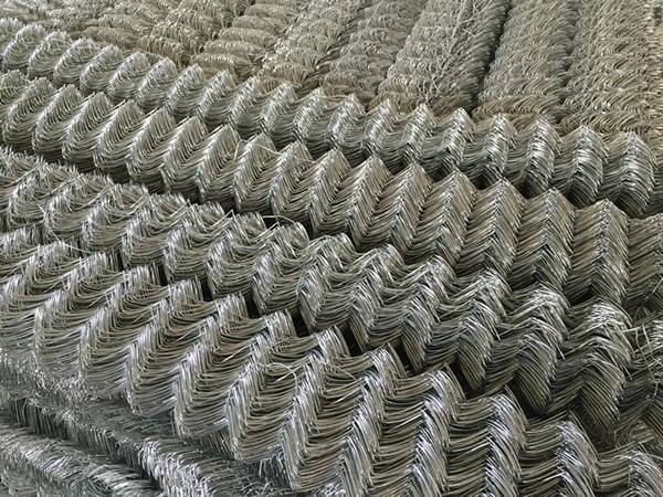Many rolls of chain link mesh neatly arranged in warehouse