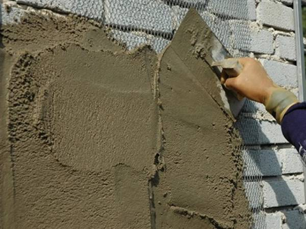 A trowel in a man's hand is plastering on a wall with expanded metal as reinforcing mesh