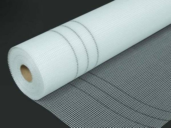 A roll of white fiberglass mesh in black background with 2×2mm mesh size