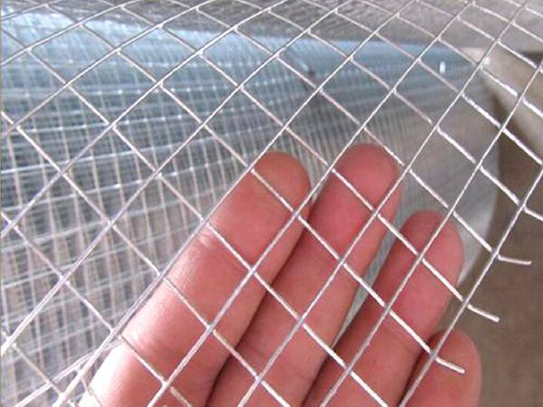 A welded wire mesh panel is held by a hand to show its detail.